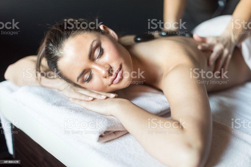 Beautiful woman being massaged with hot stones on her back stock photo