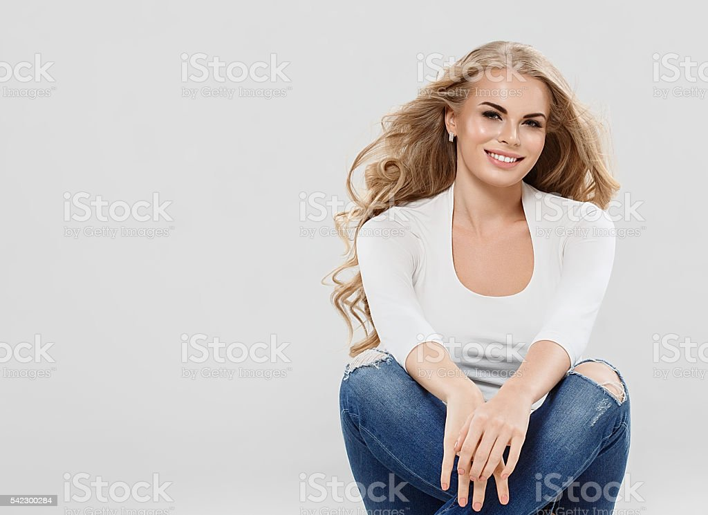 Beautiful woman blonde curly hair in jeans sitting on floor. stock photo