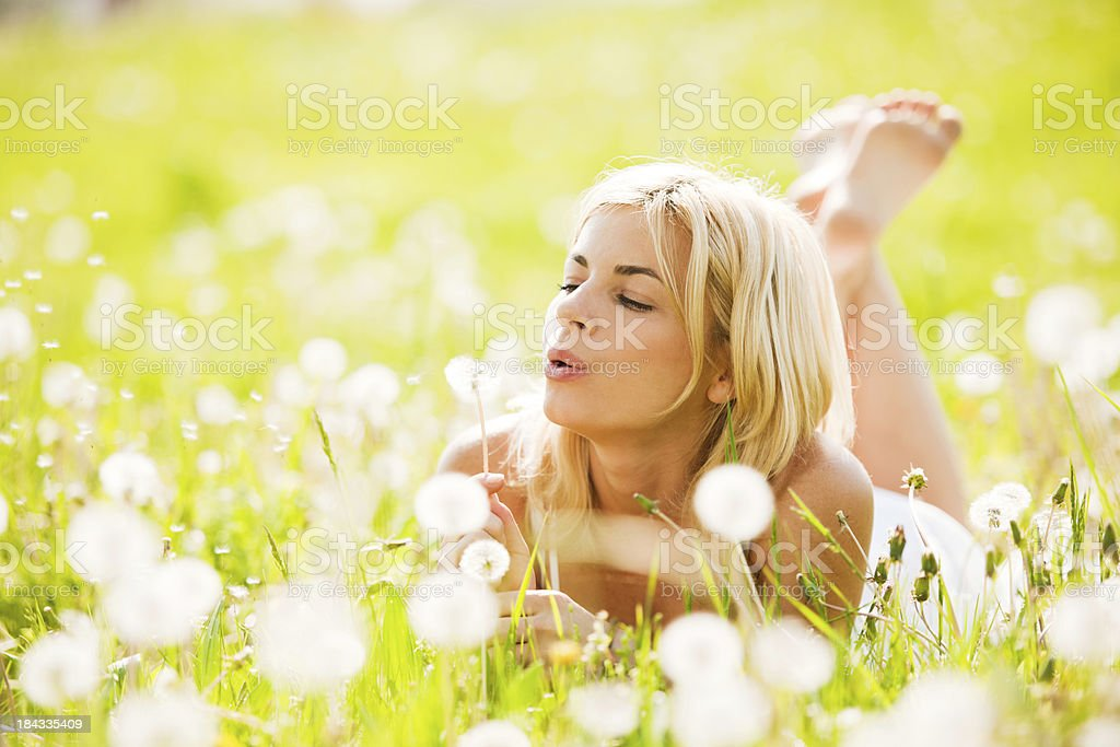 Beautiful woman blowing dandelions in the nature royalty-free stock photo