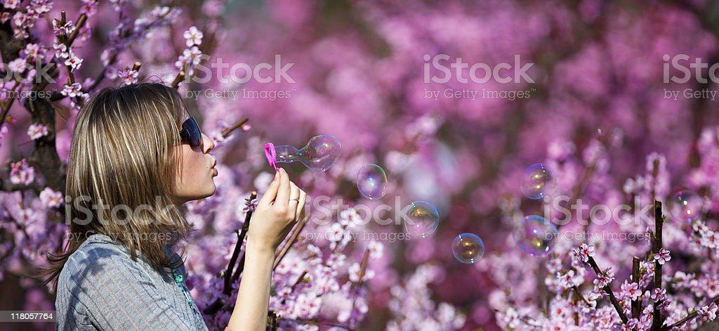 Beautiful  woman blowing soap bubbles stock photo