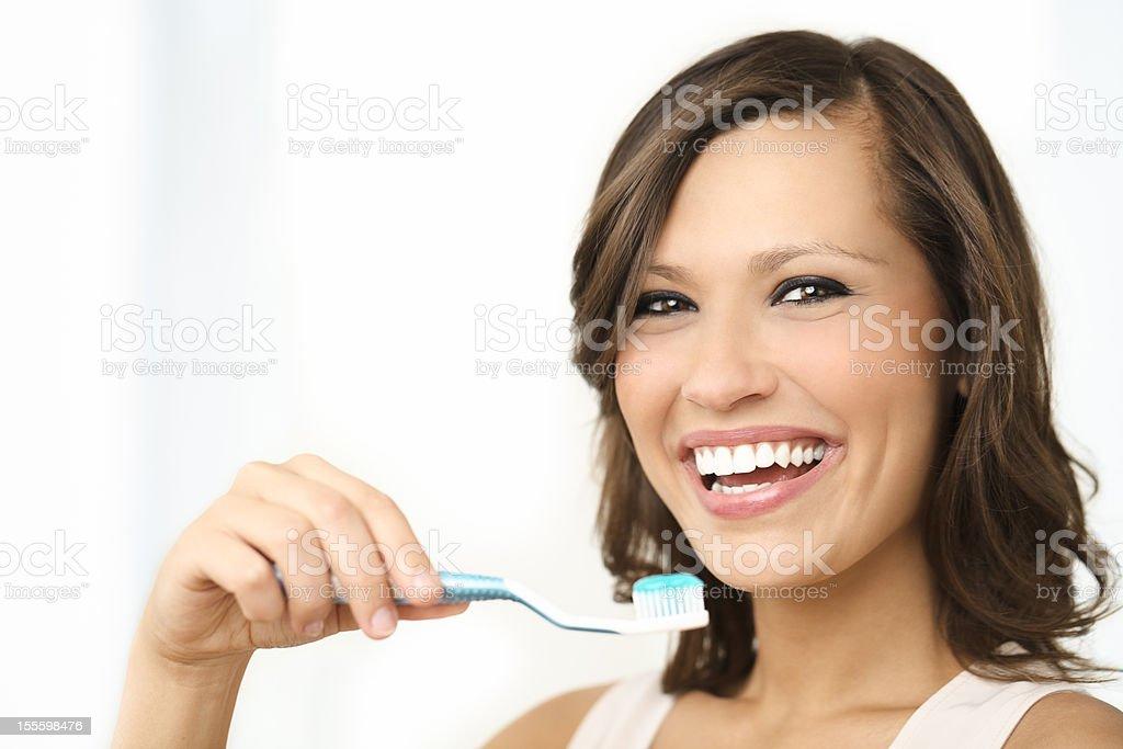 Beautiful woman brushing her teeth royalty-free stock photo