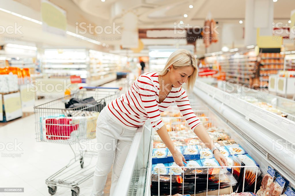 Beautiful woman buying food in supermarket stock photo