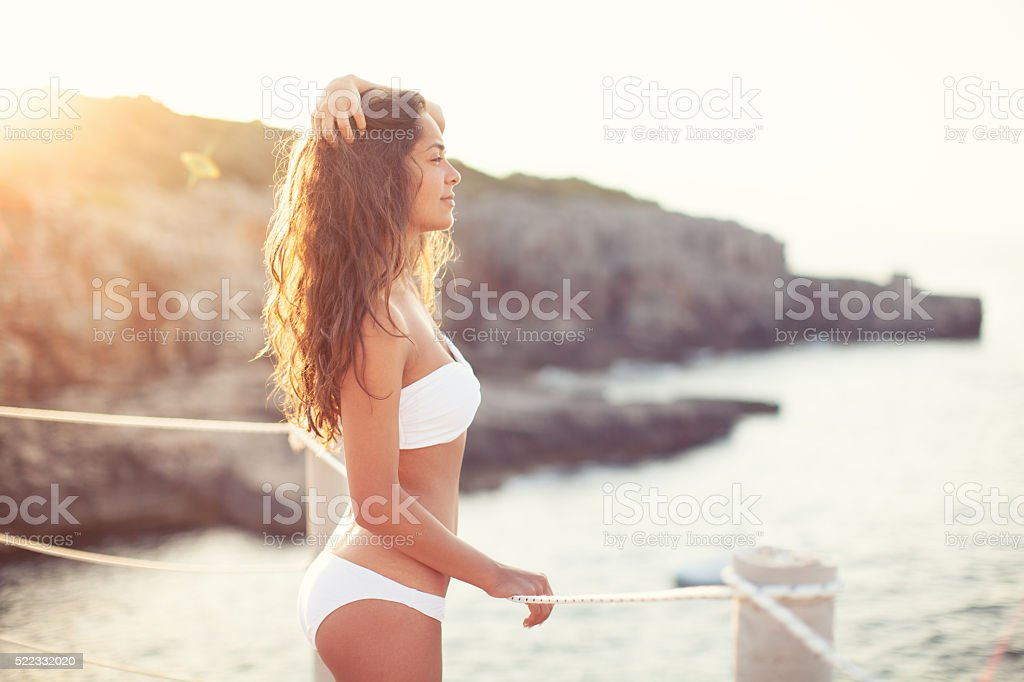 Beautiful woman by the sea stock photo