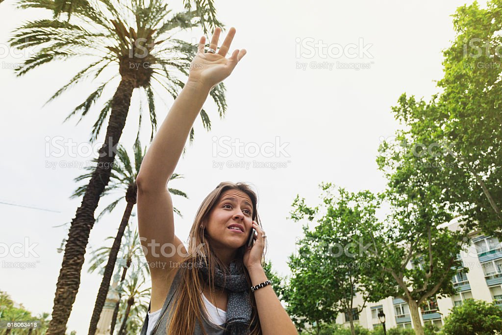 Beautiful woman calling a taxi stock photo