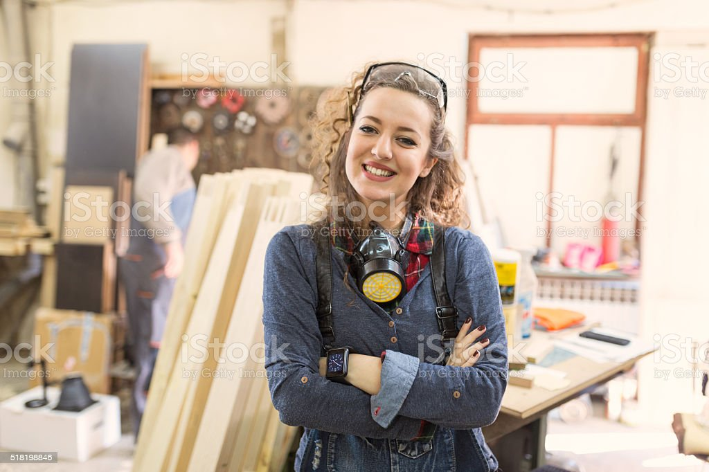 Beautiful woman carpenter wearing working clothes and smilling i stock photo