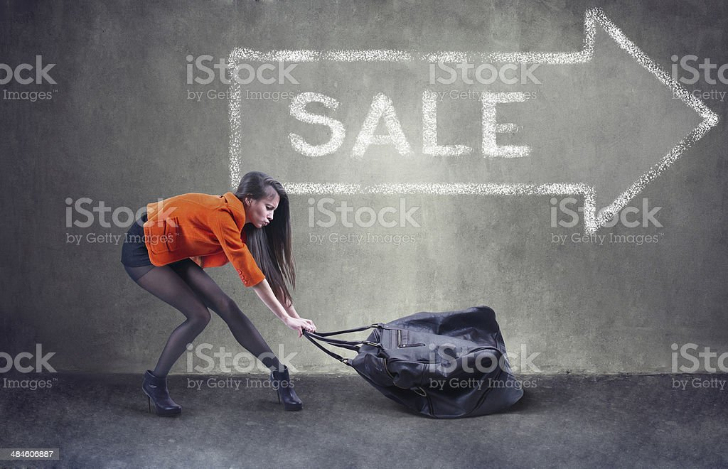 Beautiful woman carrying heavy bag with some difficulty stock photo
