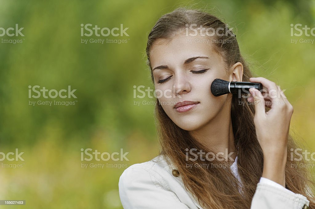 beautiful woman causes powder to face stock photo