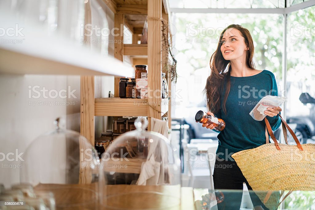 Beautiful woman choosing packets in coffee shop stock photo