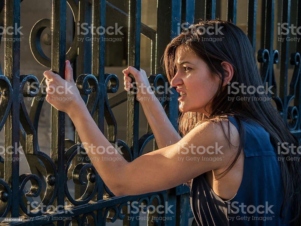 Beautiful woman claiming freedom (captive concept) stock photo