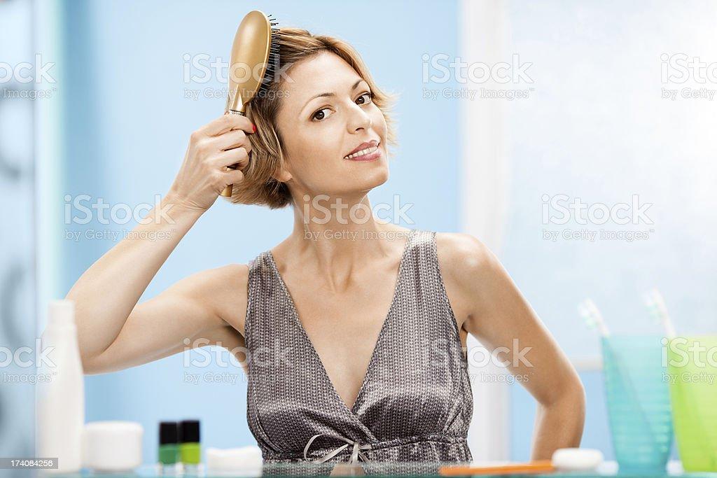 Beautiful woman combing hair royalty-free stock photo