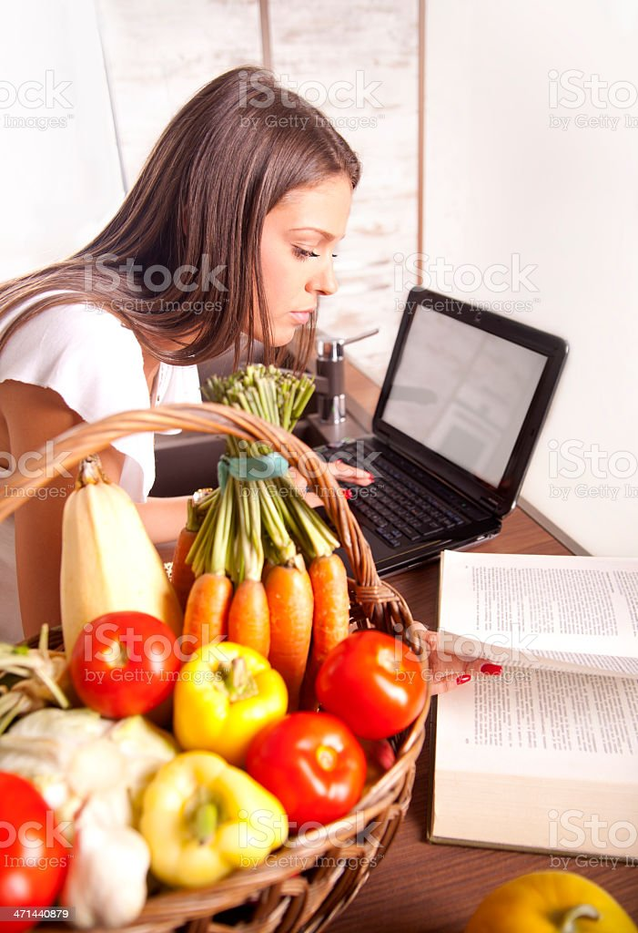 Beautiful woman cooking and looking for a recipe online royalty-free stock photo