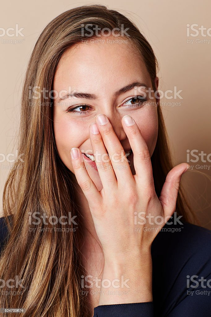 Beautiful woman covering smile in studio stock photo