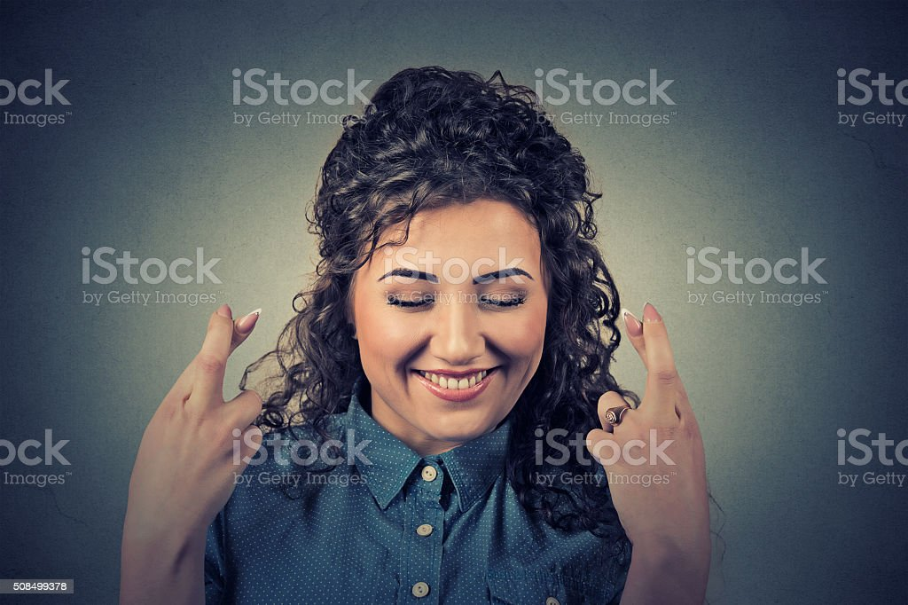 beautiful woman crossing her fingers, eyes closed stock photo