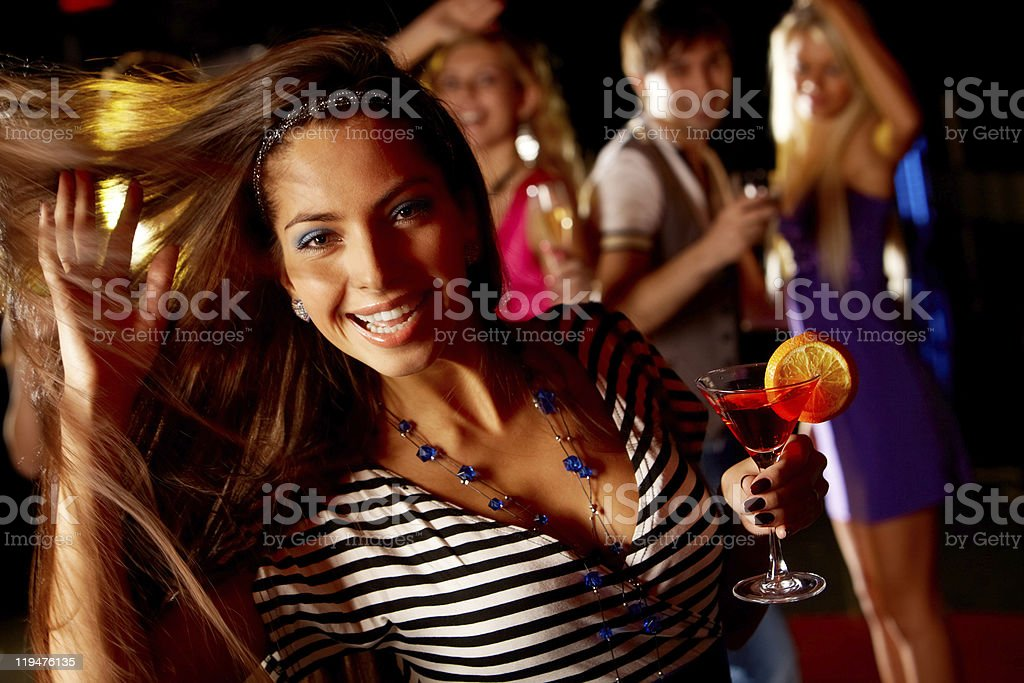 Beautiful woman dancing at party and drinking martini royalty-free stock photo