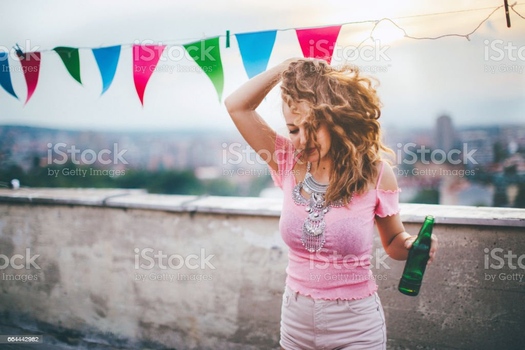 Beautiful woman dancing on rooftop party stock photo