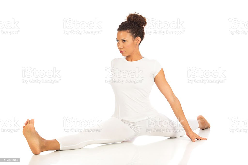 Beautiful woman doing a split, isolated on white stock photo