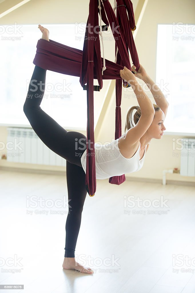 Beautiful woman doing Natarajasana yoga pose in hammock stock photo