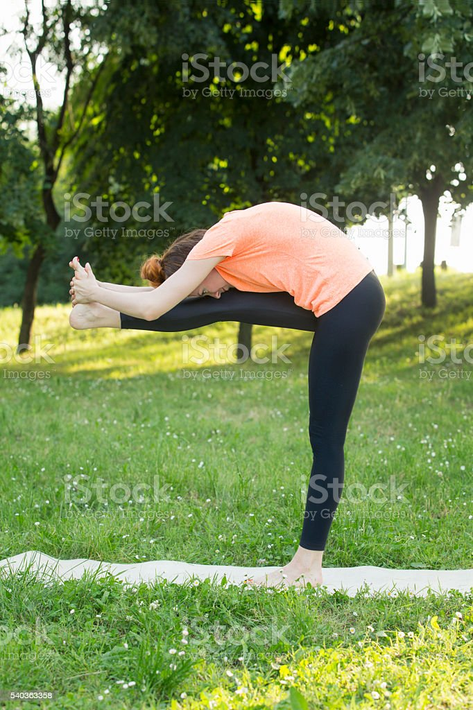Beautiful woman doing yoga in nature stock photo