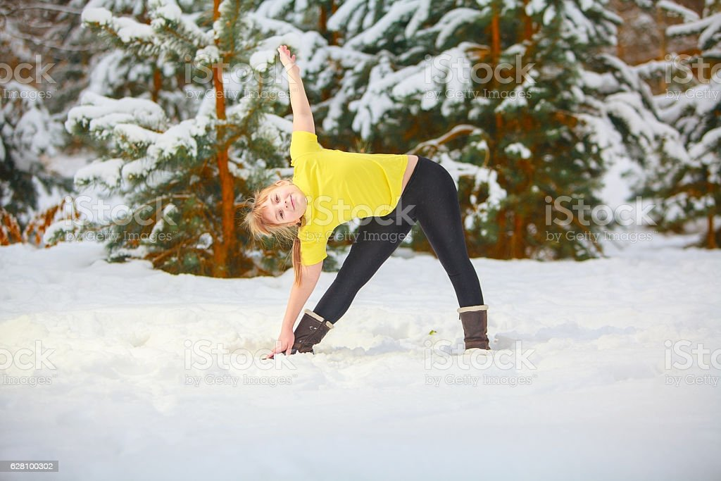 beautiful woman doing yoga outdoors in snow stock photo