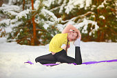 beautiful woman doing yoga outdoors in the snow