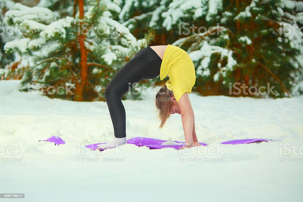 beautiful woman doing yoga outdoors in the snow stock photo