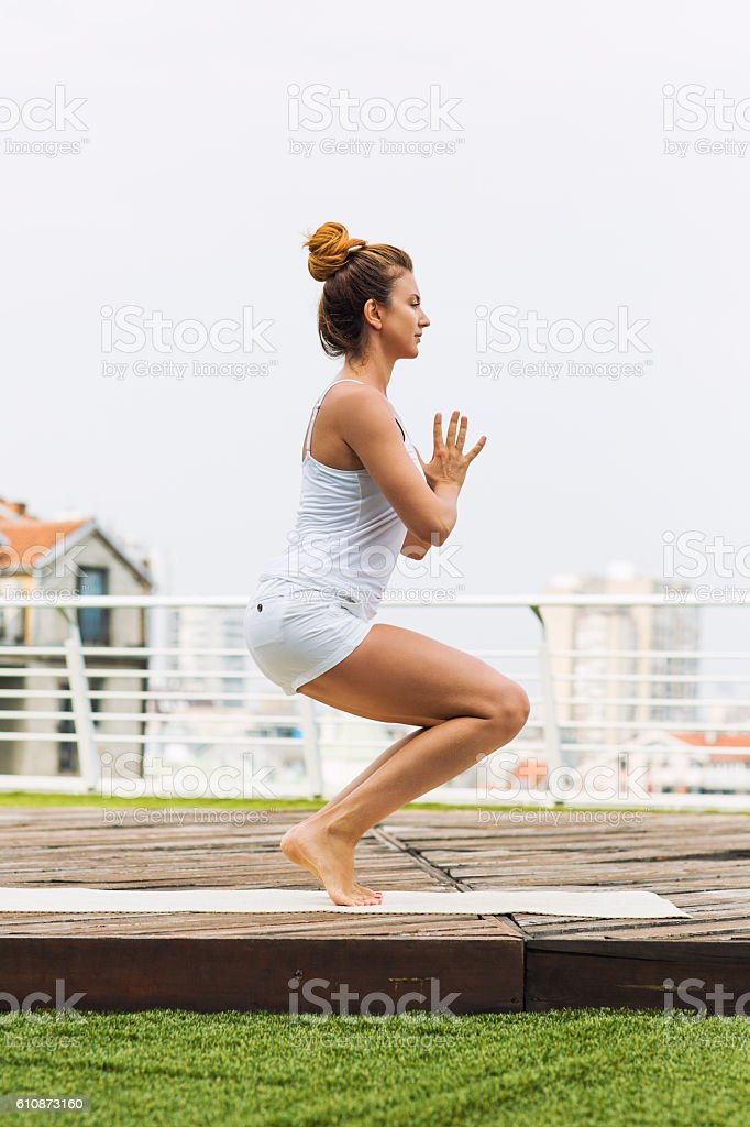 Beautiful woman doing yoga outdoors on a rooftop terrace stock photo