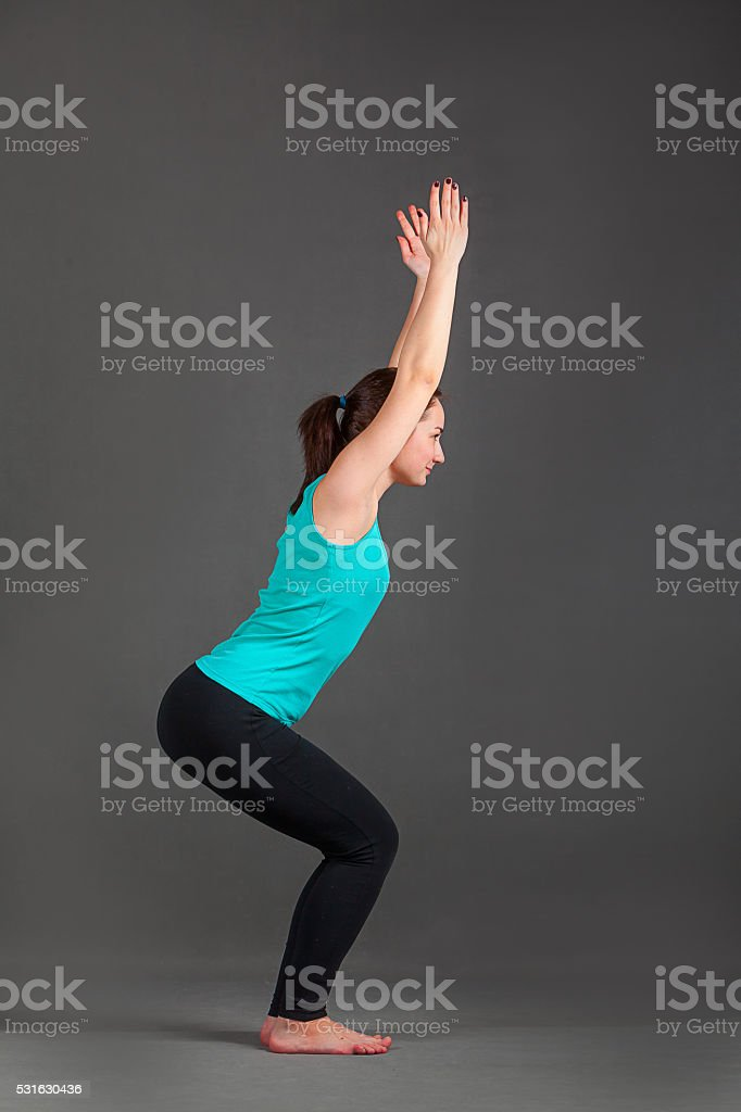 beautiful woman doing yoga utkatasana stock photo