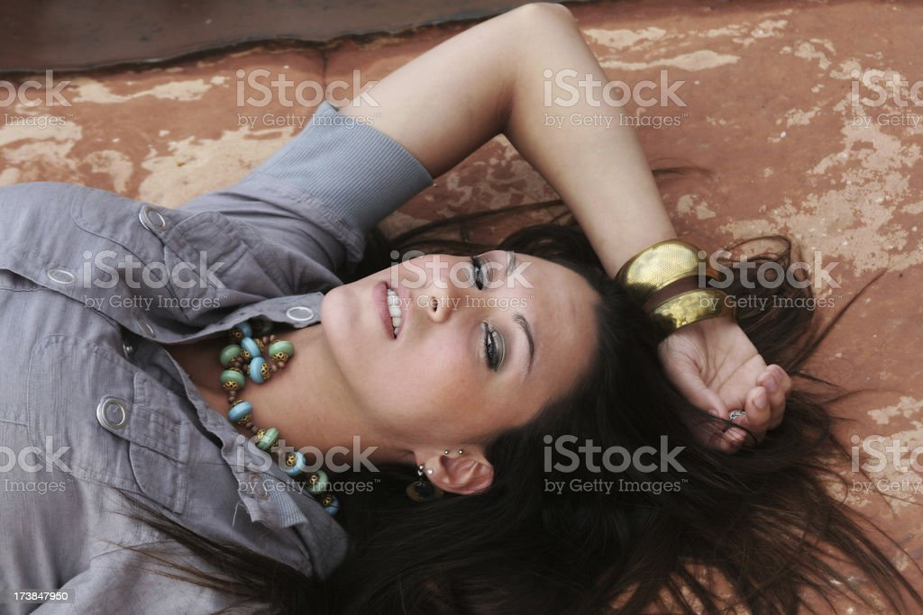 Beautiful Woman dreamily resting on red rock stock photo