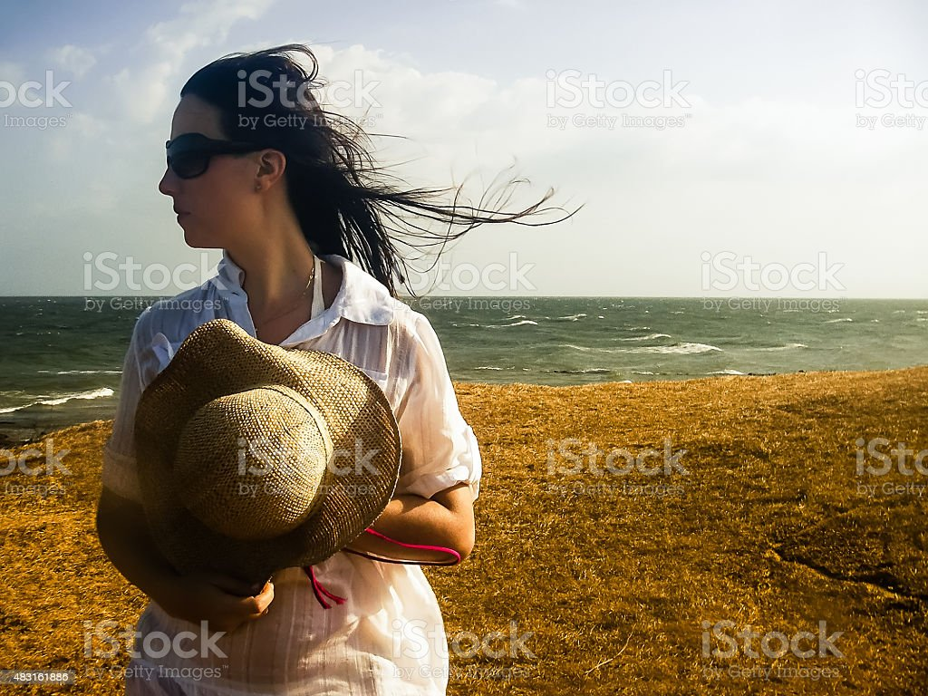 Beautiful Woman Dressed in White Holding Hat Against the Wind stock photo