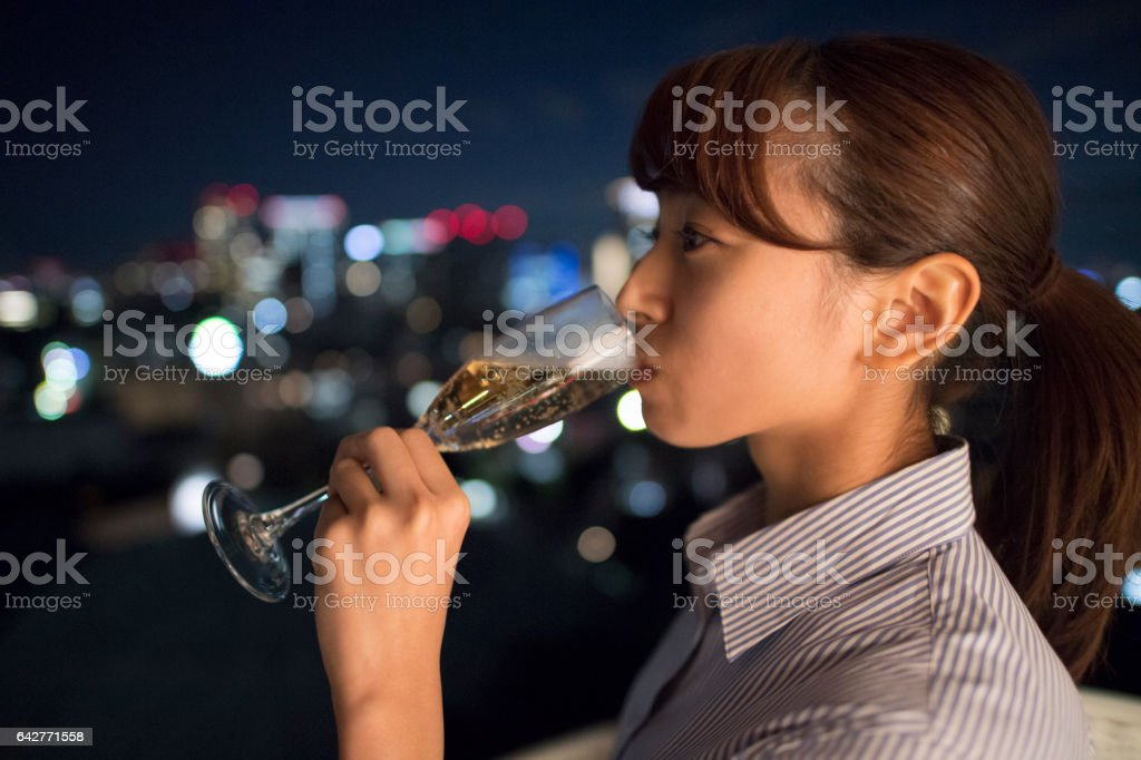 A beautiful woman drink champagne in the night. stock photo