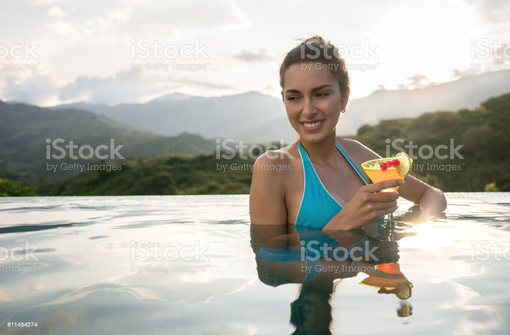 Beautiful woman drinking a cocktail in the swimming pool stock photo