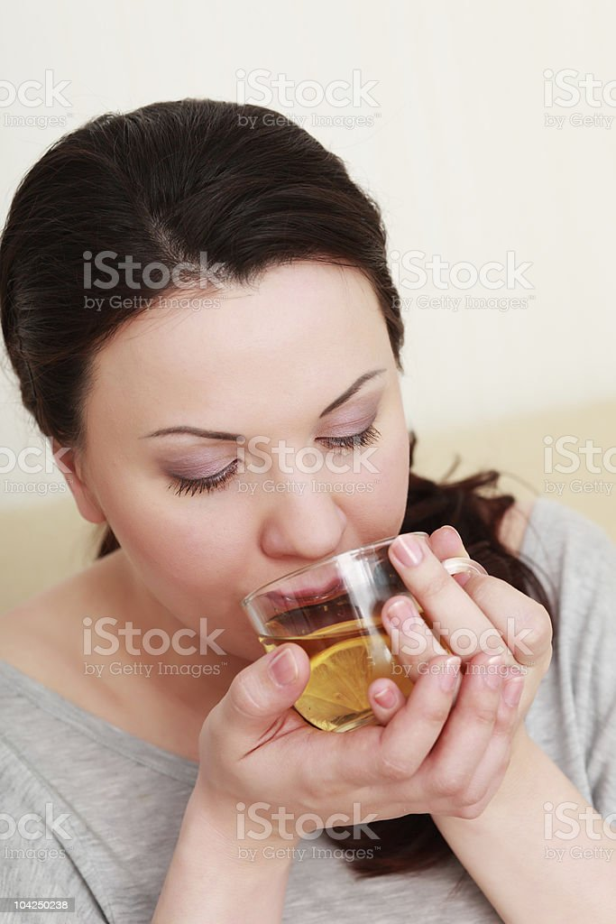Beautiful woman drinking a cup of tea with lemon stock photo
