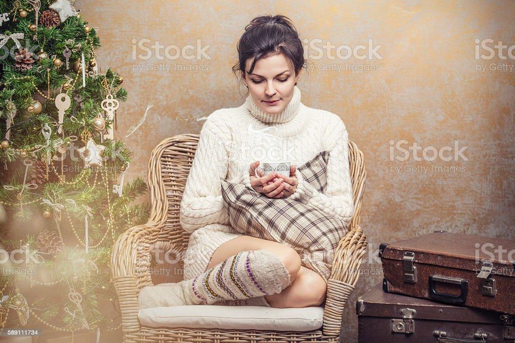Beautiful woman drinking tea or coffee sitting in a chair stock photo