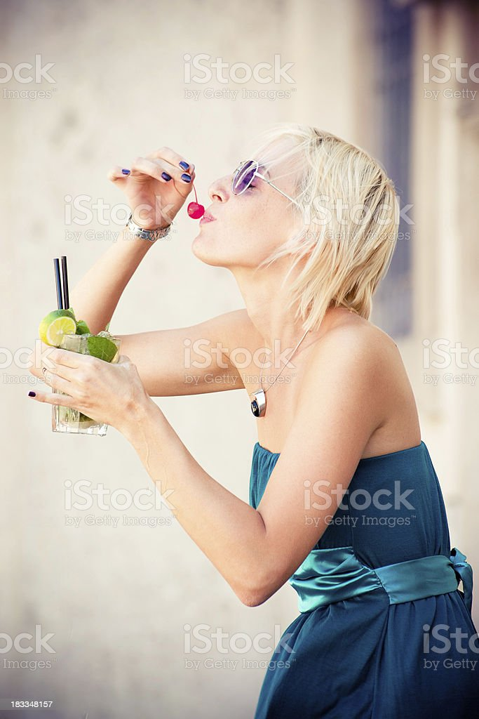 Beautiful woman eat cherry with cocktail stock photo