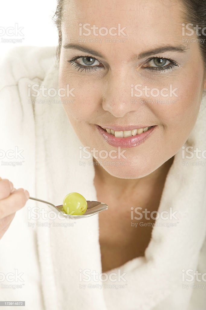 Beautiful woman eating a green grape stock photo