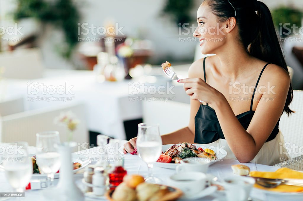 Beautiful woman eating meal in restaurant stock photo