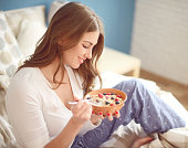 beautiful woman eating muesli with berries