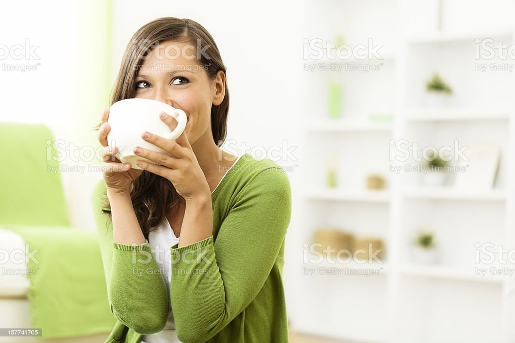Beautiful woman enjoying a cup of coffee at home stock photo