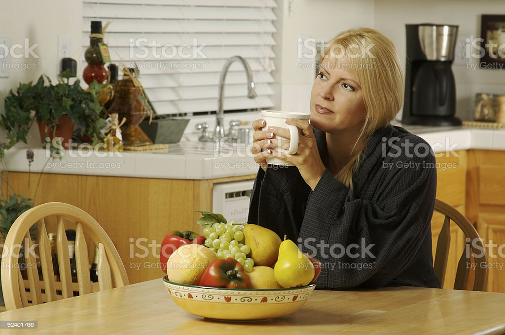 Beautiful woman enjoying a cup of coffee in kitchen. royalty-free stock photo