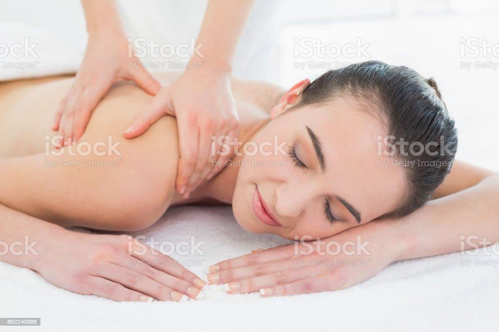 Beautiful woman enjoying back massage at beauty spa stock photo