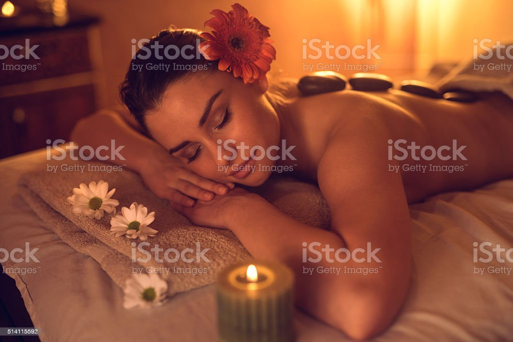 Beautiful woman enjoying during hot stone therapy at the spa. stock photo