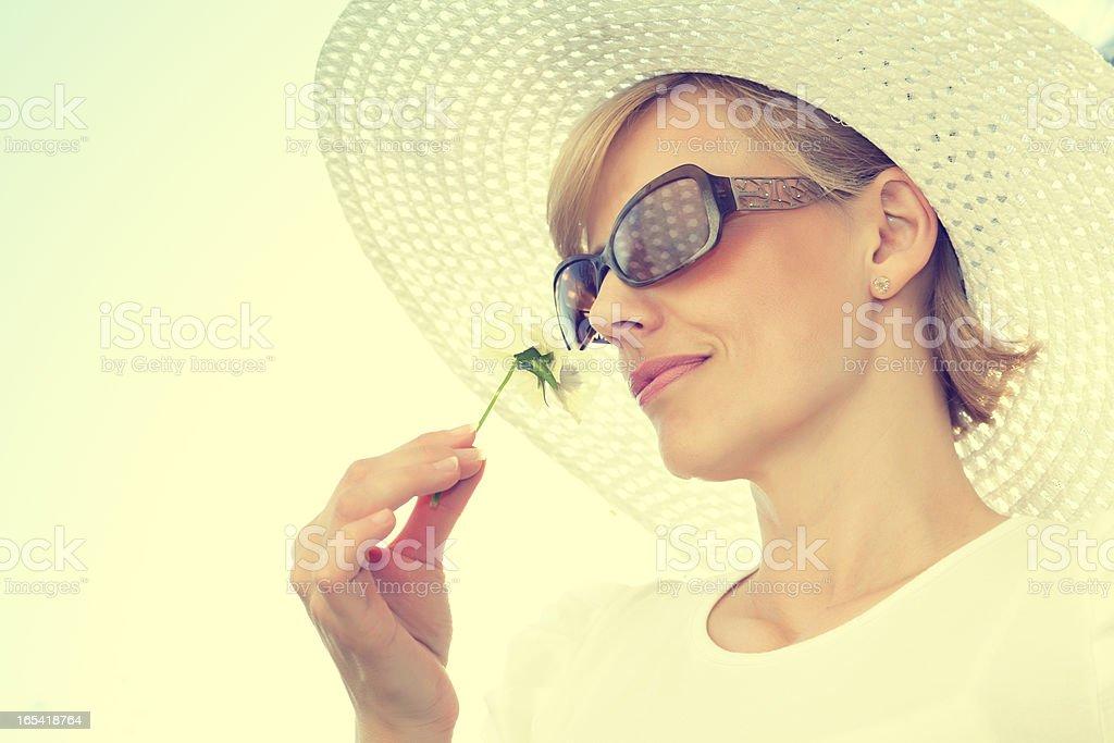 Beautiful woman enjoying flower royalty-free stock photo