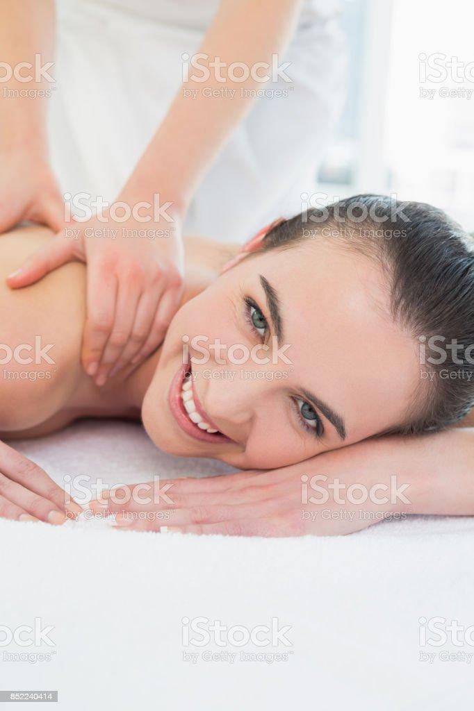 Beautiful woman enjoying shoulder massage at beauty spa stock photo