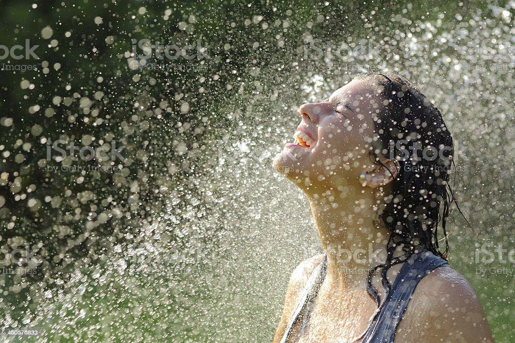 Beautiful woman enjoying under a water jet royalty-free stock photo