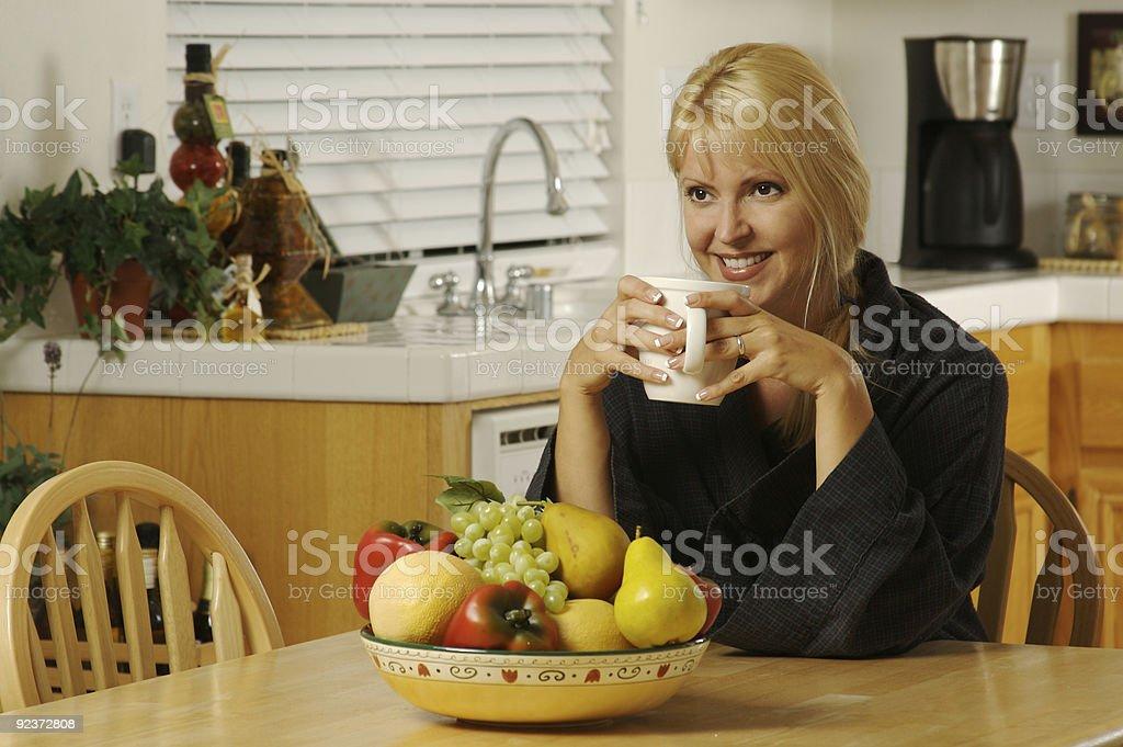 Beautiful Woman Enjoys Coffee in Kitchen royalty-free stock photo