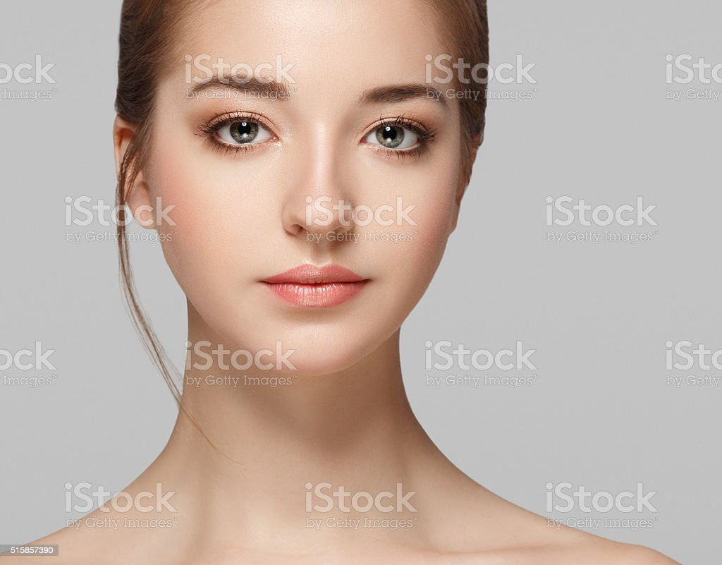 Beautiful woman face close up portrait young studio on gray stock photo