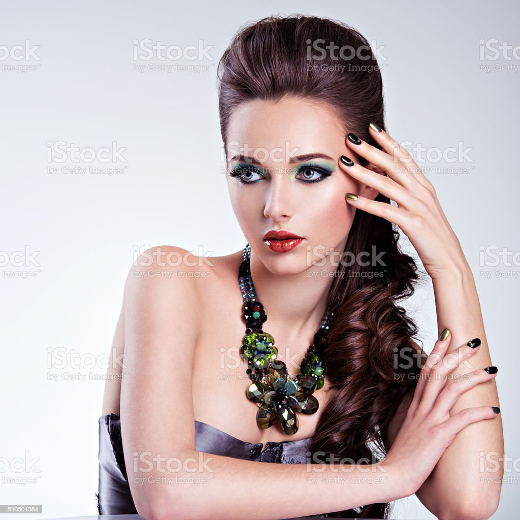 Beautiful woman face with fashion green make-up and jewelry stock photo