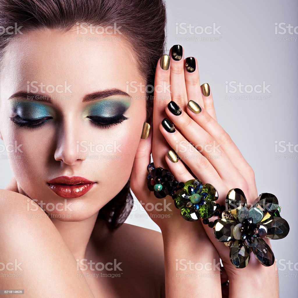 Beautiful woman face with green make-up and glass jewelry stock photo