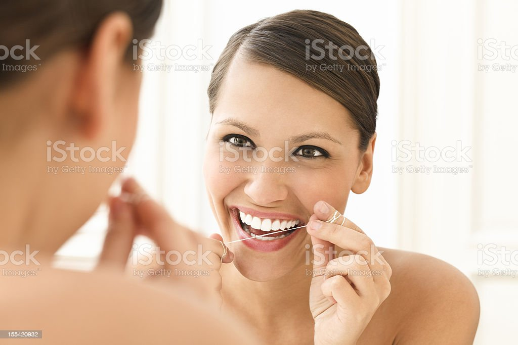 Beautiful woman flossing her teeth stock photo