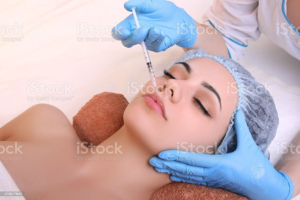 Beautiful woman gets an injection in her face. royalty-free stock photo